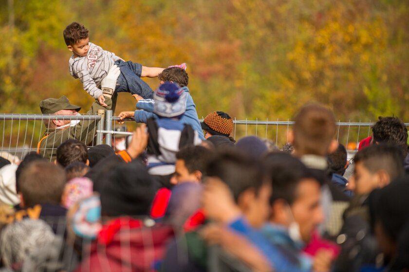 An Austrian soldier passes a child over a fence as migrants and refugees cross the Slovenian-Austrian border Oct. 25 in Sentilj.