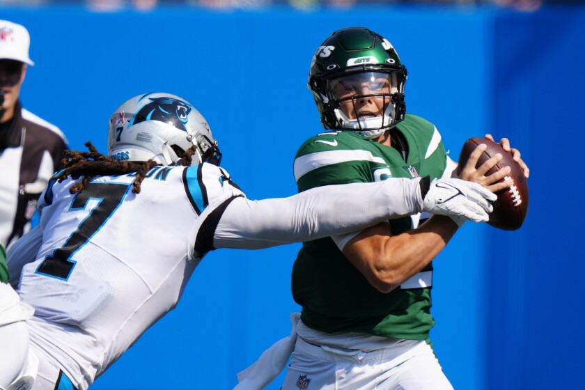 New York Jets quarterback Zach Wilson is sacked by Carolina Panthers outside linebacker Shaq Thompson during the second half of an NFL football game Sunday, Sept. 12, 2021, in Charlotte, N.C. (AP Photo/Jacob Kupferman)