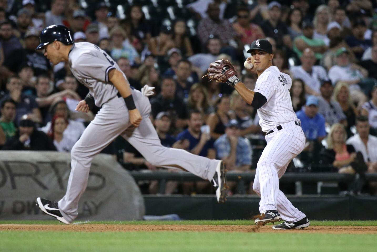 White Sox third baseman Tyler Saladino, right, winds up for the throw to first base as New York Yankees center fielder Jacoby Ellsbury heads for third base in the sixth inning.