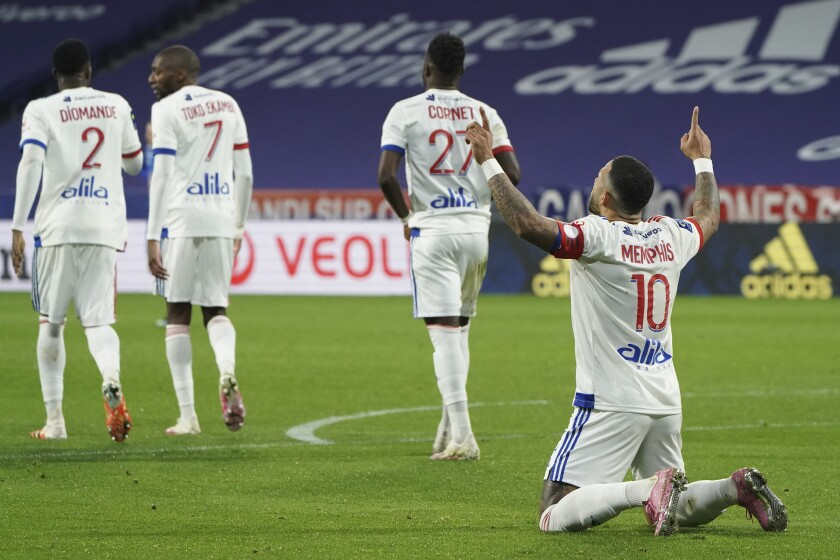 Lyon's Memphis Depay, right, celebrates his goal against Strasbourg during the French League One soccer match between Lyon and Strasbourg, in Decines, near Lyon, central France, Saturday, Feb. 6, 2021. (AP Photo/Laurent Cipriani)