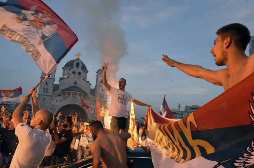 Opposition supporters celebrate after the parliamentary elections in front of the Serbian Orthodox Church of Christ's Resurrection in Podgorica, Montenegro, Monday, Aug. 31, 2020. A preliminary official tally on Monday of the country's weekend parliamentary election indicates that the pro-Western party that has ruled the country for 30 years has won the most votes, but a coalition of three opposition groupings might still take power. (AP Photo/Risto Bozovic)