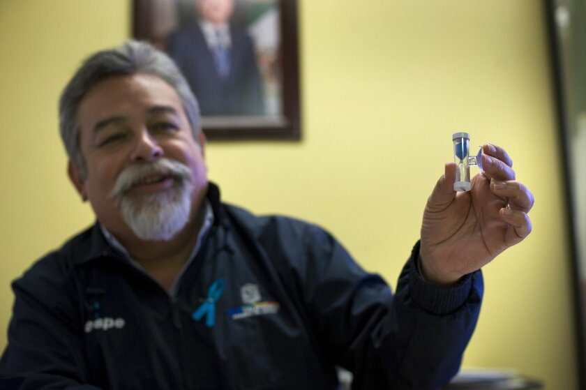 Arturo Alvarado González, head of the Cespe, Baja California's water agency in Ensenada, holds up a timer being distributed to encourage water users to limit their time in the shower.