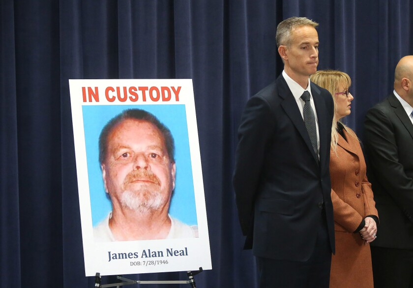 Senior Deputy District Attorney Matt Murphy, right, stands next to picture of James Alan Neal who wa