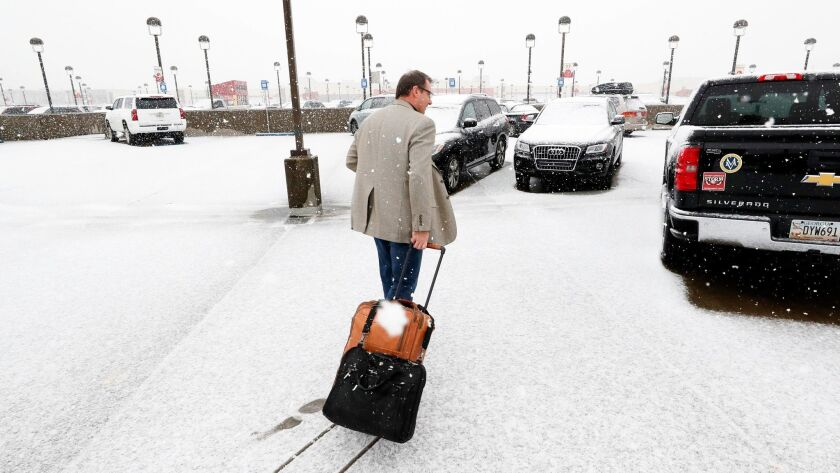 A traveller makes their way to a vehicle as snow covers the parking decks at Hartsfield-Jackson Airp