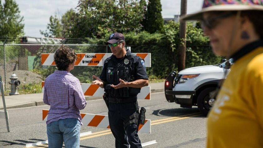 Police Officer Sam Lopez turns away would-be protesters in front of a road block near the Northwest Detention Center, Saturday July 13, 2019 in Tacoma, Wash.