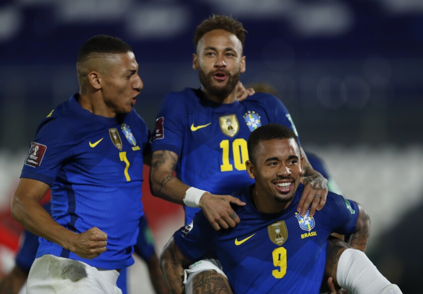 De izquierda a derecha, Richarlison, Neymar y Gabriel Jesús festejan un gol de la selección brasileña.