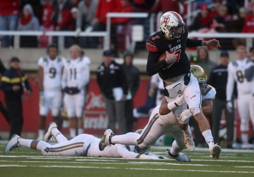 Utah quarterback Travis Wilson (7) scrambles for a first down keeping his team in scoring position late in the fourth quarter as UCLA defensive lineman Jacob Tuioti-Mariner, bottom, tries to make a tackle during an NCAA college football game on Saturday, Nov. 21, 2015 in Salt Lake City. (AP Photo/Kim Raff)