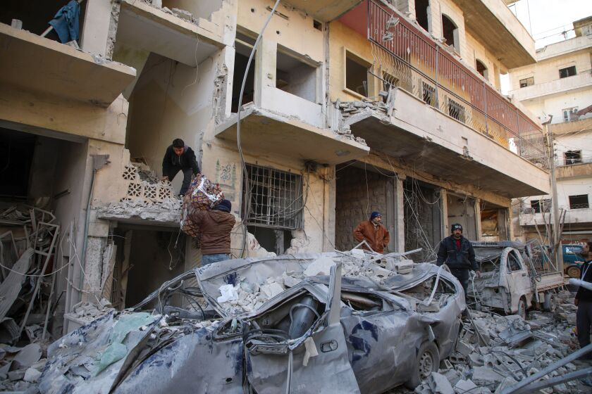 Syrians gather their belongings Jan. 30 following reported airstrikes in the town of Ariha.