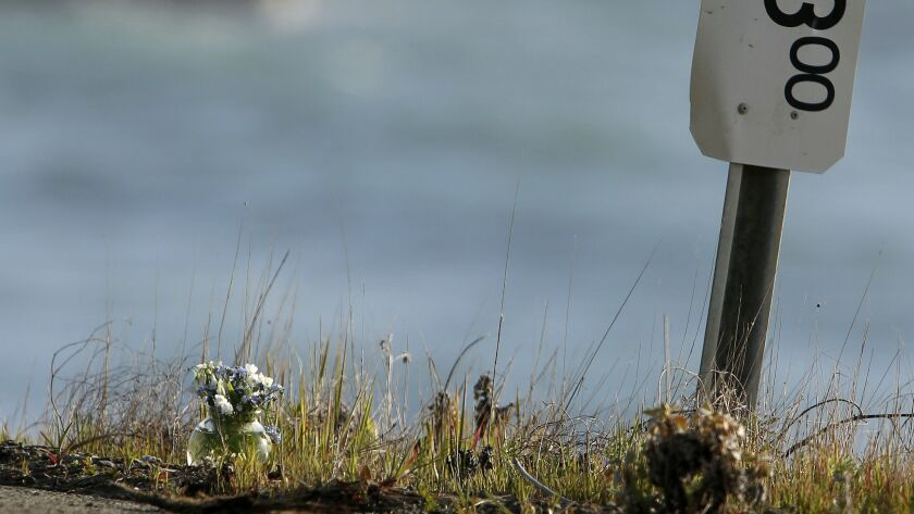 A small vase of flowers, at left, sits beside a mile marker Wednesday, March 28, 2018, near the pull