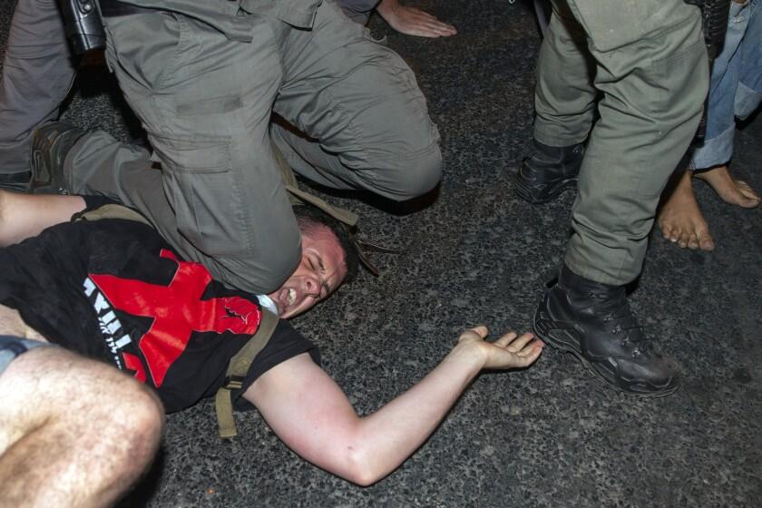 Israeli police officer puts his knee on a demonstrator