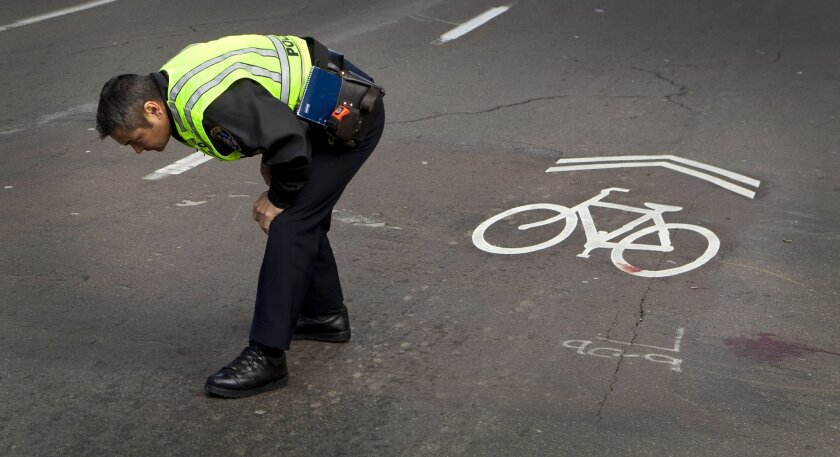 A San Diego police officer examines the scene where a bicyclist was hit by a sport utility vehicle on 4th Avenue and A Street in downtown about 2:00 p.m. A witness said the bicyclist, traveling on 4th Avenue, did not stop for the red light at A Street, and was hit by the SUV.