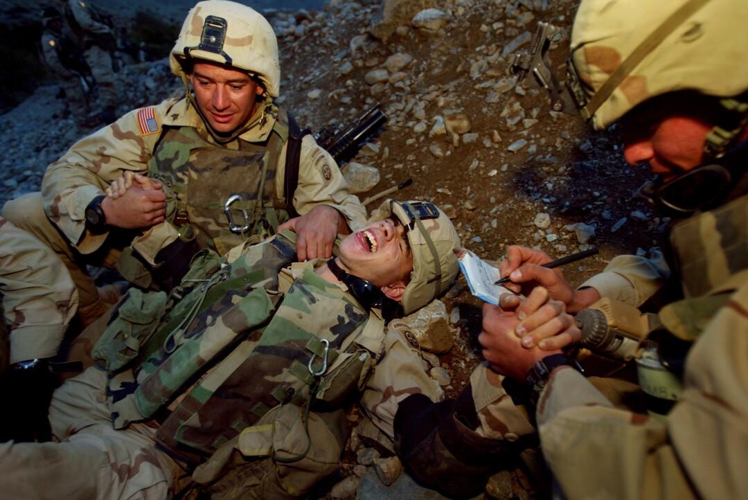 یک سرباز روی زمین دراز کشیده و فریاد می زند در حالی که سربازان دیگر او را نشانه رفته اند