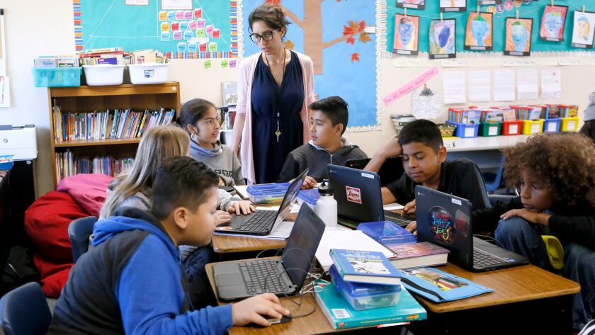 Adams Elementary School sixth grade teacher Mahtab Spera, standing, talks to her students about the