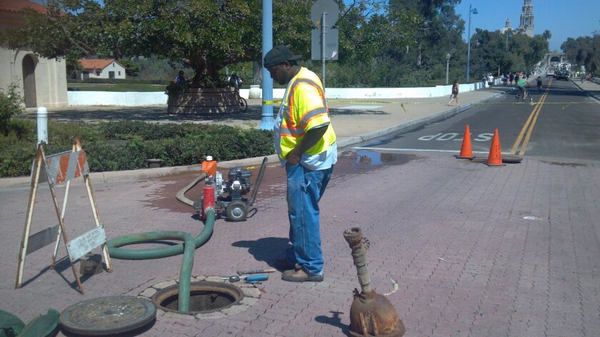 A water utilities crew member awaits delivery of a replacement part before reopening the Cabrillo Bridge to traffic following a water main break.