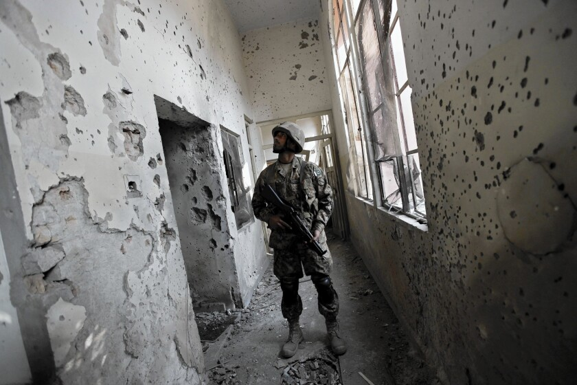 A soldier looks at bullet holes at the public school in Peshawar, Pakistan, where Taliban militants killed 132 students and 16 staff members two days earlier.