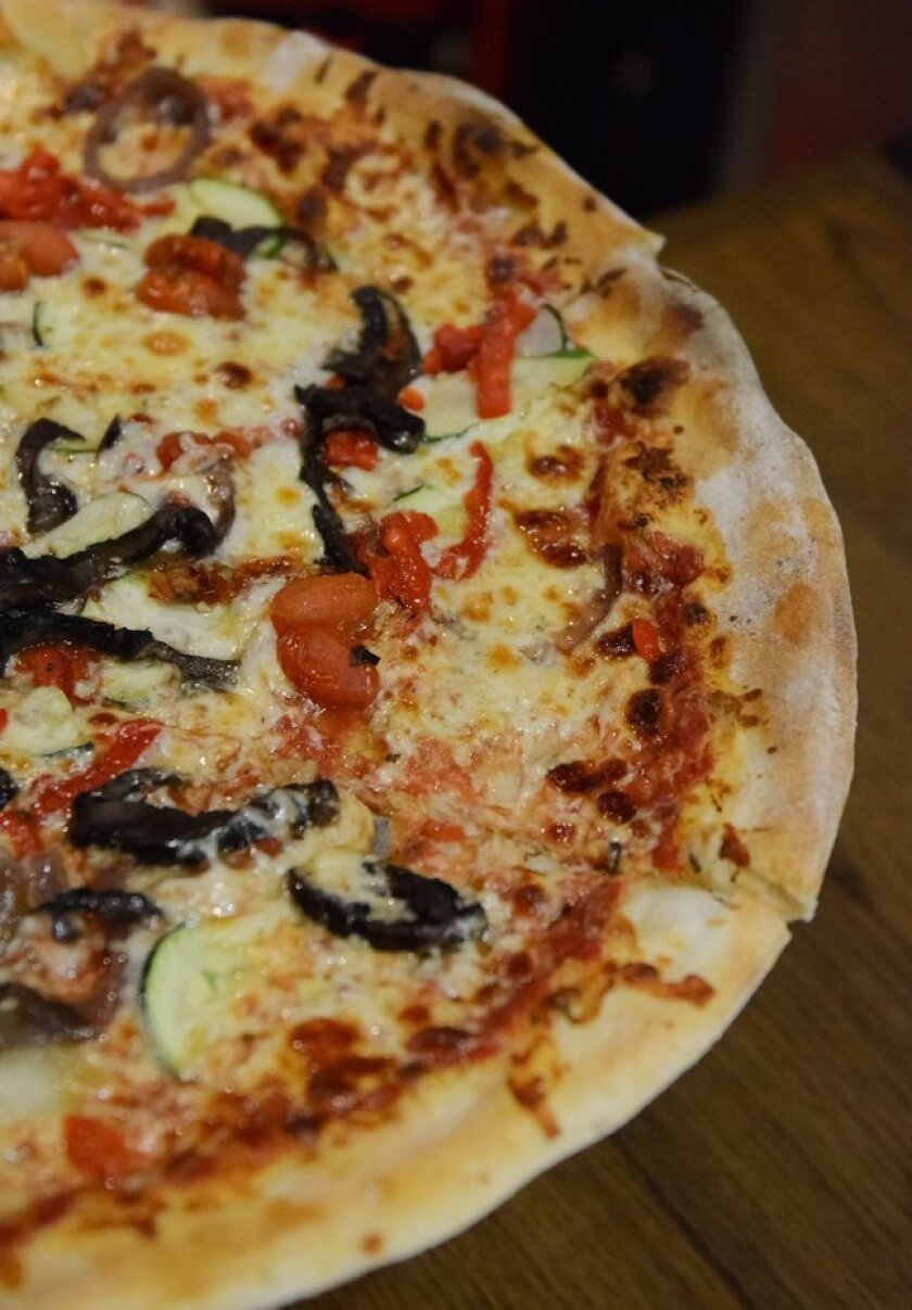 This New York-style Veggie Pizza features marinated portobello mushrooms, semi-dried tomatoes, roasted red peppers, grilled onions, zucchini and provolone at Regents Pizzeria in La Jolla.