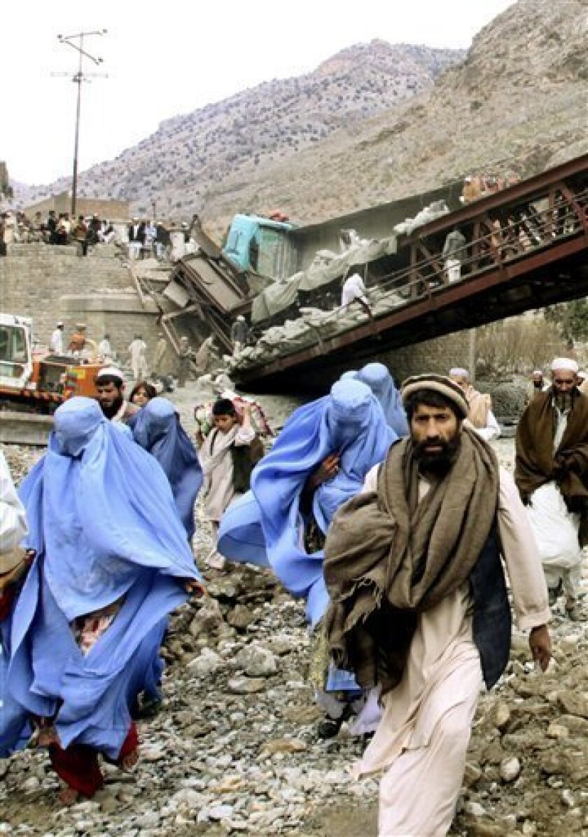 Local residents walk past a bridge destroyed by alleged Islamic militants Tuesday, Feb. 3, 2009 in the Pakistani tribal area of Khyber, near Peshawar. Islamic militants blew up the bridge in northwest Pakistan, cutting a major supply line for western troops in Afghanistan, a government official and a NATO spokesman said. The attack was the latest in a series on the Khyber Pass by insurgents seeking to hamper the US-led mission against the Taliban in neighboring Afghanistan. (AP Photo/Mohammad Sajjad)