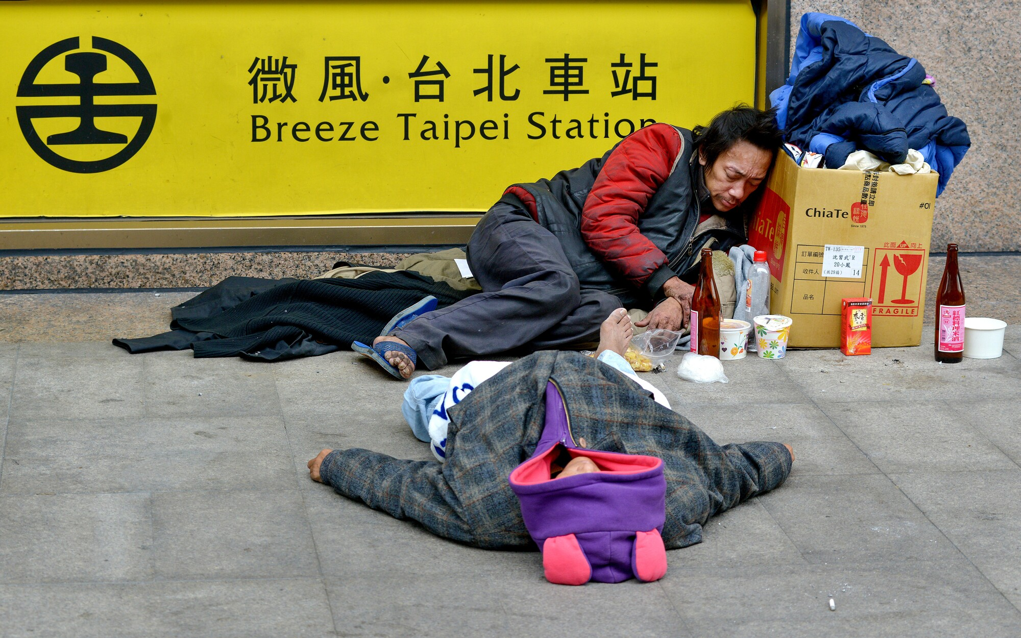 Homeless people drunk on cooking wine at the main train station in Taipei, Taiwan.