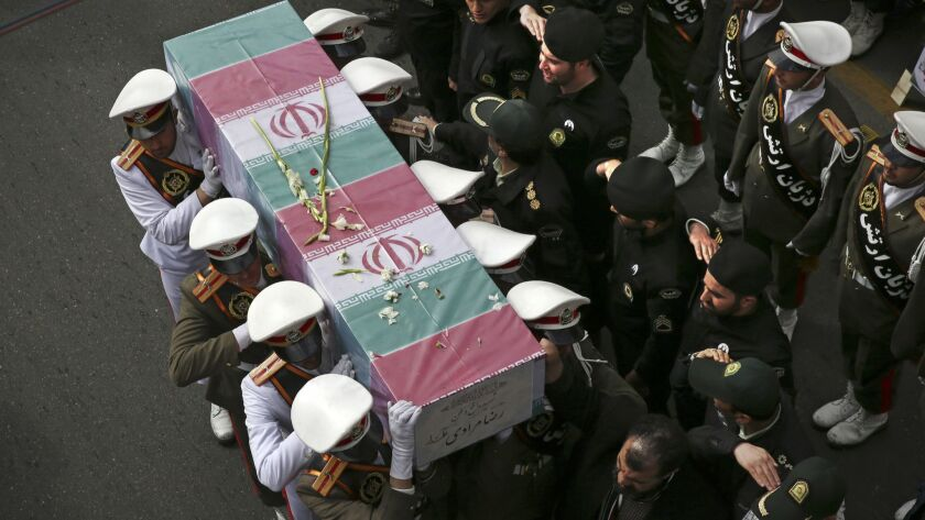 FILE - In this Feb. 22, 2018 file photo, Iranian policemen carry a flag-draped coffin of their colle