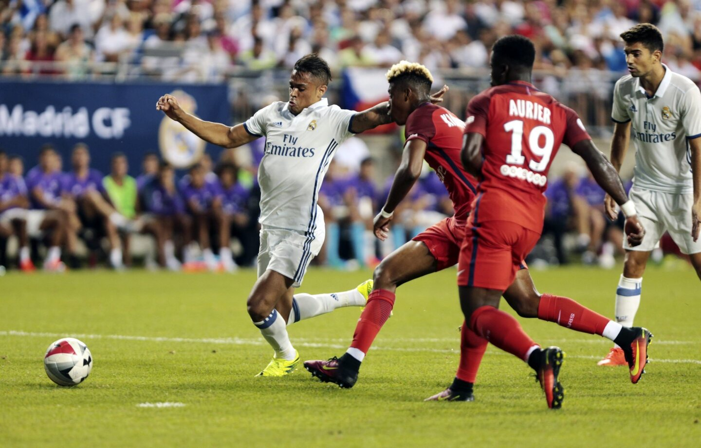 Serge Aurier (d) y Presnel Kimpembe (c) de Paris Saint-Germain en acción ante Mariano Díaz (i) de Real Madrid durante un partido por la International Champions Cup en el estadio Ohio en Columbus, Ohio (Estados Unidos).