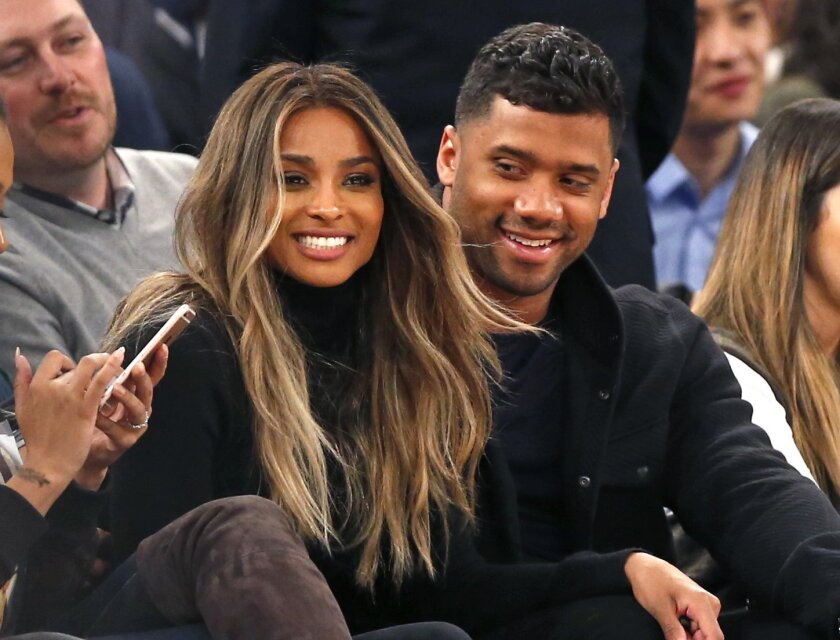 FILE - In this Feb. 9, 2016 file photo, singer Ciara, second from left, and Seattle Seahawks quarterback Russell Wilson sit courtside while attending an NBA basketball game between the New York Knicks and the Washington Wizards in New York. The couple were married Wednesday, July 6, 2016, at Peckfo