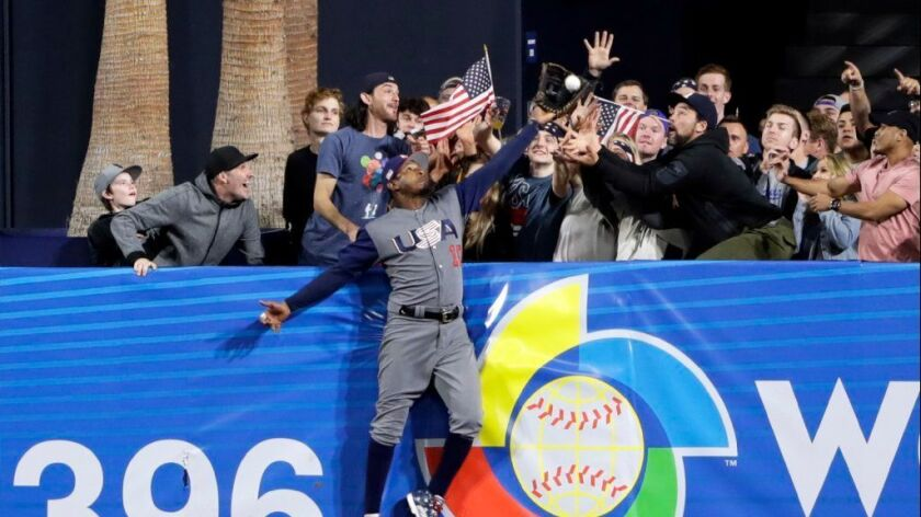 U.S. outfielder Adam Jones makes a catch above the wall, stealing a home run from the Dominican Republic's Manny Machado during the seventh inning of a World Baseball Classic game on March 18.