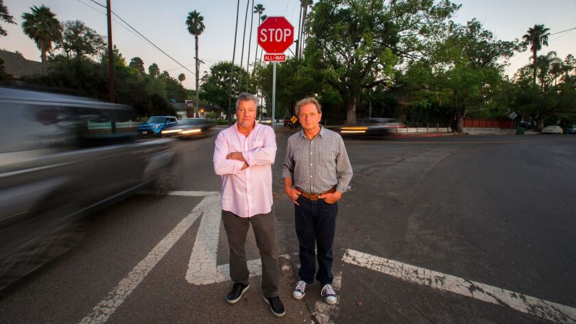 Rob Ramsey, left, and Alexander Von Wechmar spent 12 years pushing for a traffic circle at a dangerous intersection on their street. When the city said it didn't have the cash, they raised funds themselves.