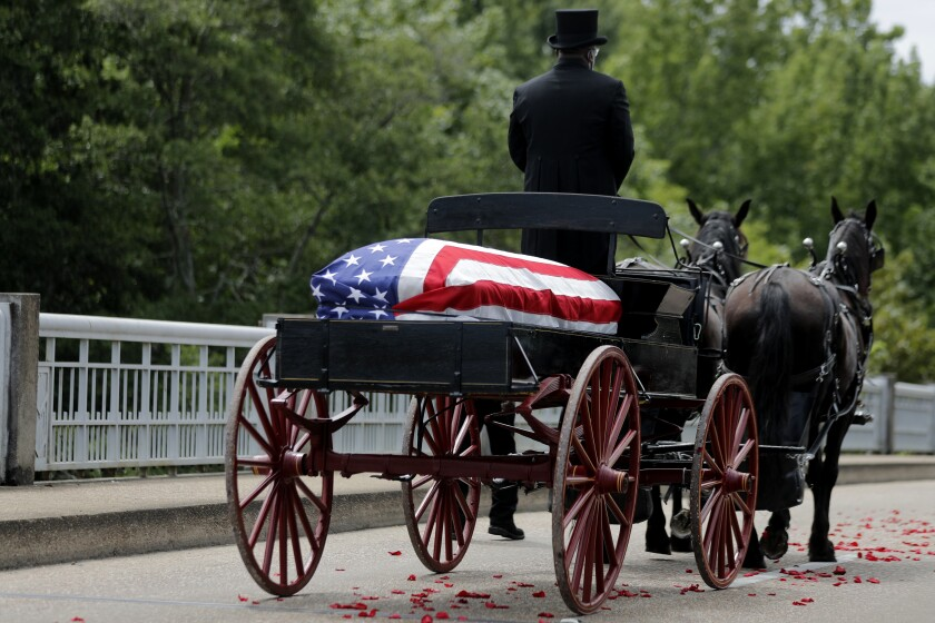 The casket of Rep. John Lewis moves over the Edmund Pettus Bridge by horse drawn carriage during a memorial service for him.