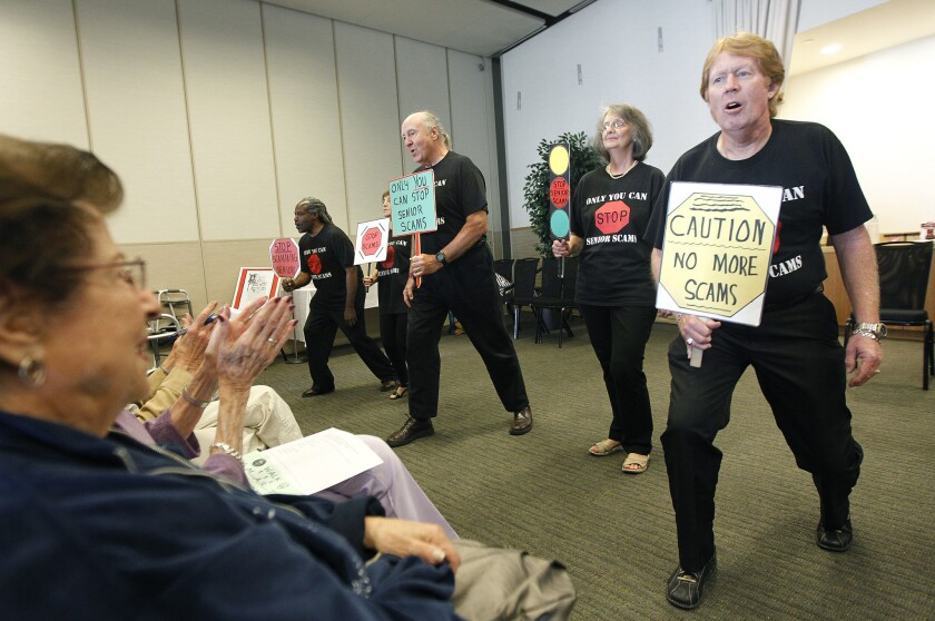 Participants with the Stop Senior Scams Acting Program, including Jimi Poulin, 65, right, perform a skit at Temple Judea in Tarzana.