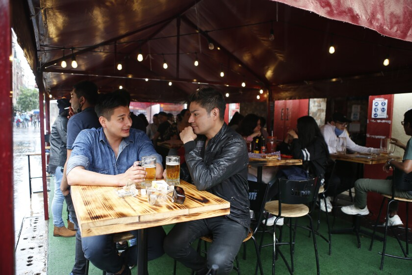 Luis Alvarez, 27, left, and Pablo Quintero, 35, right, drink beer at a bar in Mexico City, Saturday, July 10, 2021. Mexico is entering its third wave of the coronavirus pandemic. The country's health department said Friday the growth is largely coming from infections among younger, less vulnerable people. (AP Photo/Ginnette Riquelme)