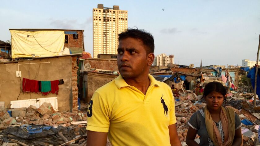 Santosh Gond spent thousands to renovate his house months before it was torn down. Behind him is the