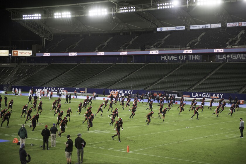 San Diego State warms up under the lights of a near empty stadium.