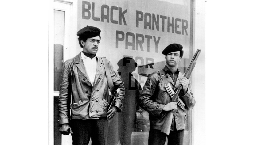 Black Panther Party co–founders Bobby Seale, left, and Huey Newton stand watch in front of the party headquarters in Oakland during the late 1960s.