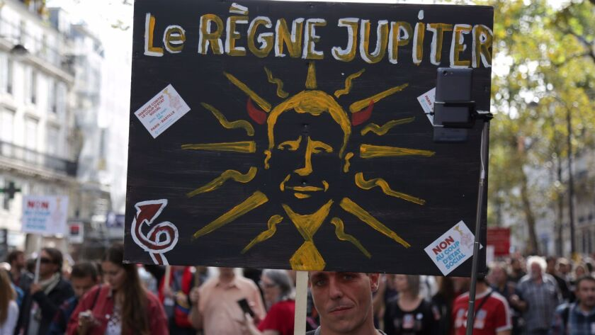 """A demonstrator holds a sign reading """"The reign of Jupiter"""" during a Sept. 23, 2017, protest in Paris"""