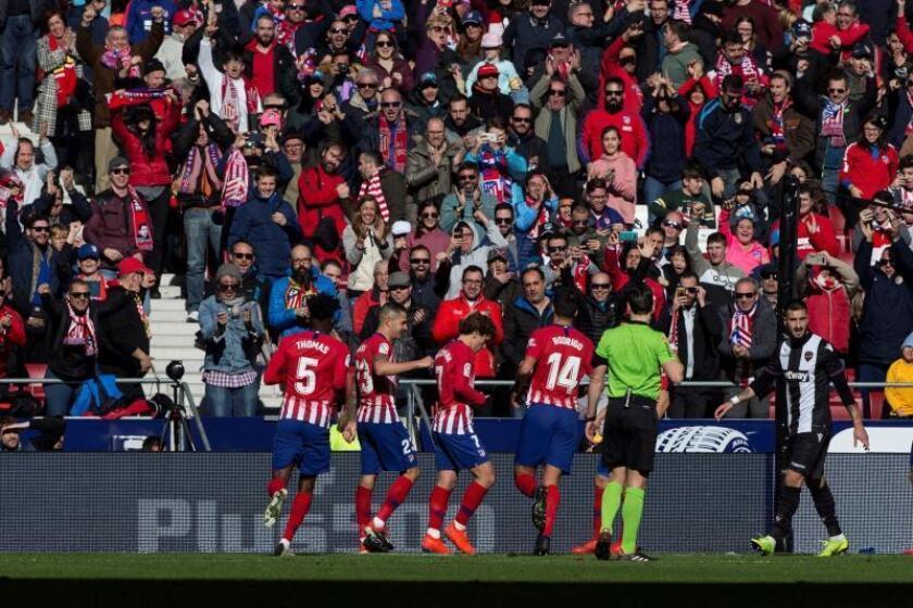 El delantero francés del Atlético de Madrid Antoine Griezmann (c) celebra con sus compañeros el gol marcado de penalti al Levante, durante el partido de la décima novena jornada de Liga de Primera División disputado esta mañana en el Wanda Metropolitano. EFE