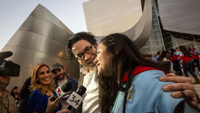 El director de la Filarmónica de Los Ángeles, Gustavo Dudamel, y la violoncelista de la Orquesta Juvenil de Los Ángeles, Karla Melgar, son entrevistados por reporteros de televisión afuera del Disney Hall en el downtown de L.A.