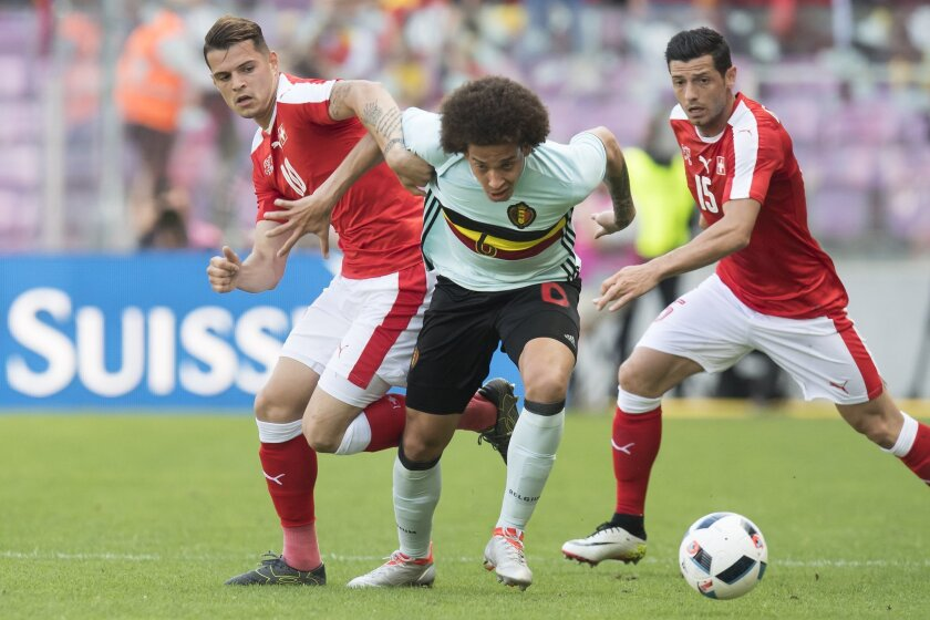 Swiss forward Granit Xhaka, left, challenges for the ball with Belgian Axel Witsel, center, next to Swiss midfielder Blerim Dzemaili, right, during a friendly soccer match between Switzerland and Belgium, at the stade de Geneve stadium, in Geneva, Switzerland, Saturday, May 28, 2016. (Jean-Christop