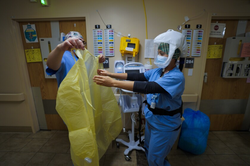 Nurses put on new gloves and gowns before entering a room with patient who has COVID-19.