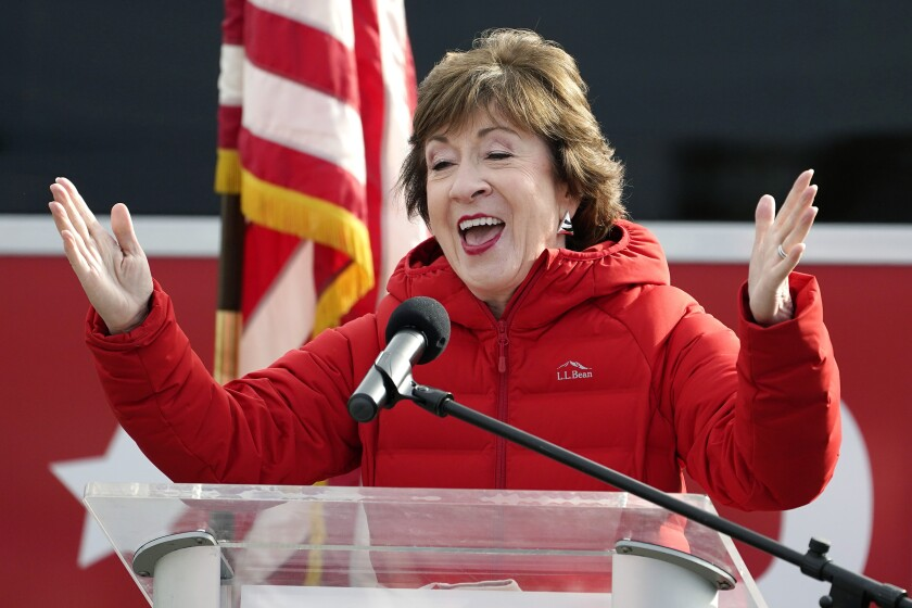 Senator Susan Collins in a red down jacket gestures with both hands in excitement while speaking at a lectern