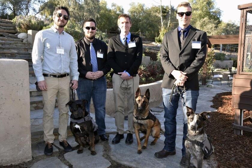 Dog trainers Vince Martell with Julio, recipient Ben Kilhefner, Stephen Snyder with Jax, and Perry Chapman with Bandit