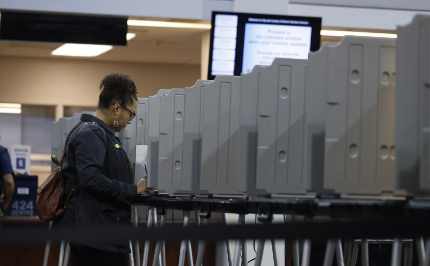FILE—In this Tuesday, Nov. 5, 2020, file photo, a lone voter fills out a ballot in the lobby of the Denver Elections Division in downtown Denver. Colorado voters head to the polls to cast their ballots in the state's primary election Tuesday, March 3. (AP Photo/David Zalubowski, File)