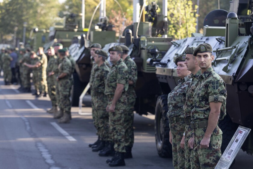 """Serbian army soldiers stand to attention in front of armored personnel carriers on display as part of a newly established """"Serbian Unity Day"""" holiday in Belgrade, Serbia, Wednesday, Sept. 15, 2021. Serbia has kicked off a new holiday celebrating national unity with a display of military power, triggering unease among its neighbors. The new holiday comes decades after similar calls for unity led to the bloody wars in the Balkans in the 1990s. Serbs in the region were told to display thousands of red, blue and white national flags wherever they live in the region or the world to mark """"The Day of Serb Unity, Freedom and the National Flag."""" Serbian officials are calling for the creation of a """"Serb World,"""" or political unification of an estimated 1.3 million Serbs who live in Bosnia, Montenegro, Kosovo and Croatia with Serbia. (AP Photo/Marko Drobnjakovic)"""