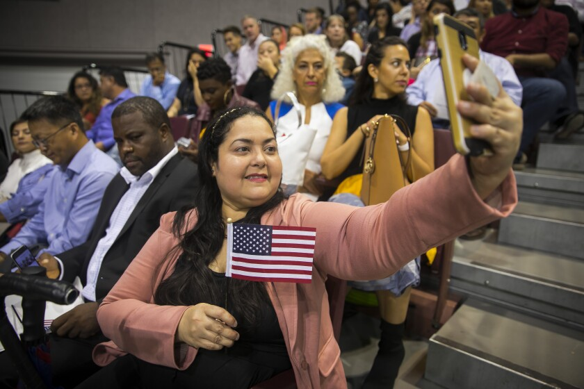 Nirhosky Griffin takes a selfie with a small American flag as she waits for her naturalization ceremony to begin in Houston.
