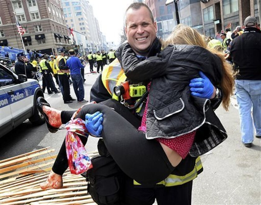 In this Monday, April 15, 2013 photo, Boston Firefighter James Plourde carries an injured girl away from the scene after a bombing near the finish line of the Boston Marathon in Boston. The FBI's investigation into the bombings at the Boston Marathon was in full swing Tuesday, with authorities serving a warrant on a suburban Boston home and appealing for any private video, audio and still images of the blasts that killed at least three and wounded more than 170. (AP Photo/MetroWest Daily News, K