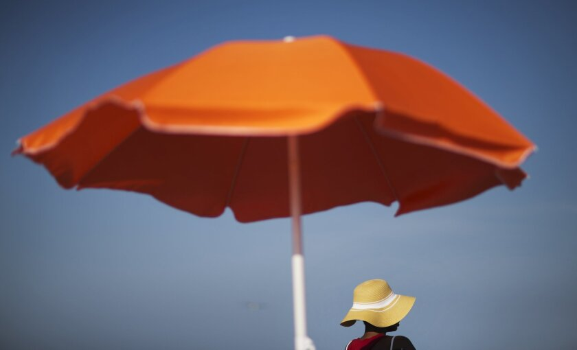 FILE - In this Tuesday, June 16, 2015, file photo, a woman sits next to an umbrella while looking out toward the ocean in Folly Beach, S.C. That sunscreen in your bag may not protect your skin as much as you think. Even after regulators updated standards for labeling sunscreen in 2012, tests have s