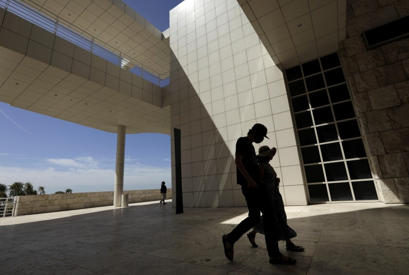 Silhouettes of visitors walking in front of the white tiled buildings of the Getty Center
