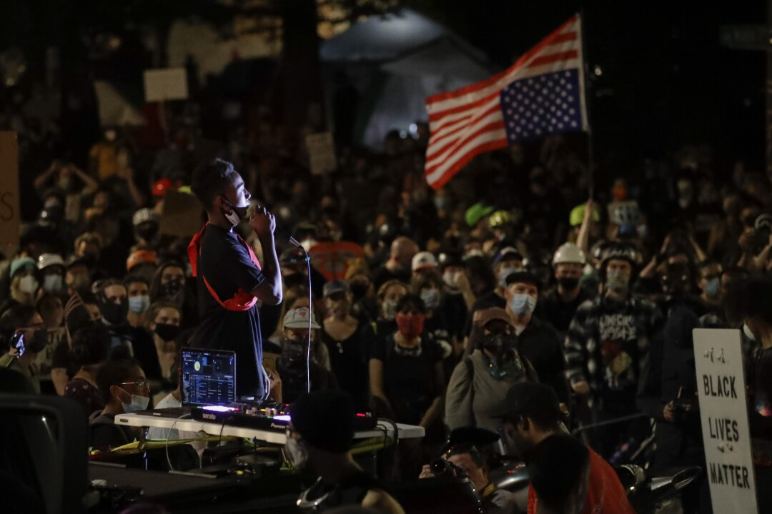 A demonstrator speaks to a crowd from the bed of a pickup truck during a Black Lives Matter protest in Portland, Ore.