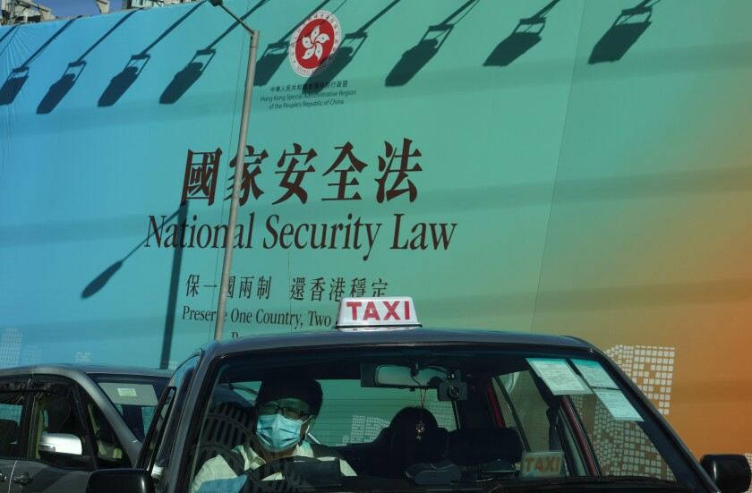 A taxi drives past a banner touting the Hong Kong National Security Law.