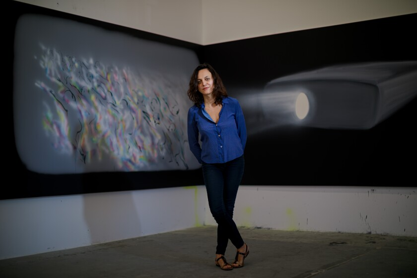 """Tala Madani stands before the diptych """"Corner Projection (Panic),"""" 2019, in her Los Angeles studio."""
