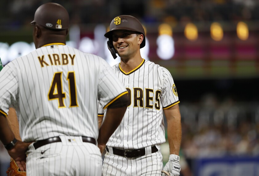 After getting is first hit with the Padres, Adam Frazier smiles as he talks with Wayne Kirby